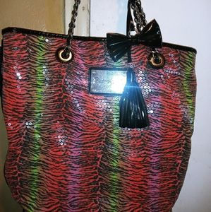 A colorful shoulder bag with pink interior.